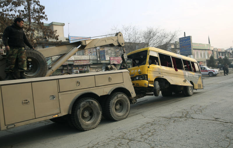 An Afghan National Army (ANA) truck removes a destroyed ANA minibus from the site of a suicide attack in Kabul, Afghanistan, Sunday, Jan. 26, 2014. An Afghan official said a suicide bomber attacked a military bus in Kabul, killing at least four people. (AP Photo/Massoud Hossaini)