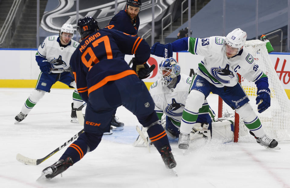 Edmonton Oilers' Connor McDavid (97) takes a shot on Vancouver Canucks goalie Braden Holtby (49) as Bo Horvat (53) defends during the second period of an NHL hockey game Wednesday, Jan. 13, 2021, in Edmonton, Alberta. (Dale MacMillan/The Canadian Press via AP)