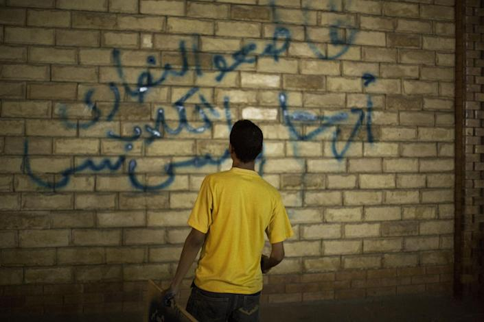 """A supporter of ousted Egyptian President Mohammed Morsi paints graffiti on the wall of a Coptic Church in Assiut, Upper Egypt, Tuesday, Aug. 6, 2013. Islamists may be on the defensive in Cairo, but in Egypt's deep south they still have much sway and audacity: over the past week, they have stepped up a hate campaign against the area's Christians. Blaming the broader Coptic community for the July 3 coup that removed Islamist president Mohammed Morsi, Islamists have marked Christian homes, stores and churches with crosses and threatening graffiti. Arabic graffiti reads, """"Boycott the Christian dogs."""" (AP Photo/Manu Brabo)"""