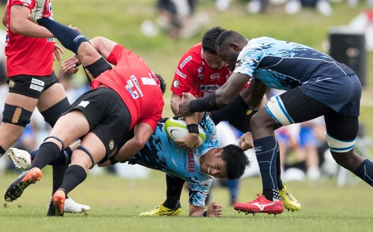 Yamaha Jubilo's Shohei Awata (C) is tackled by Kamaishi Seawaves' players during their memorial match