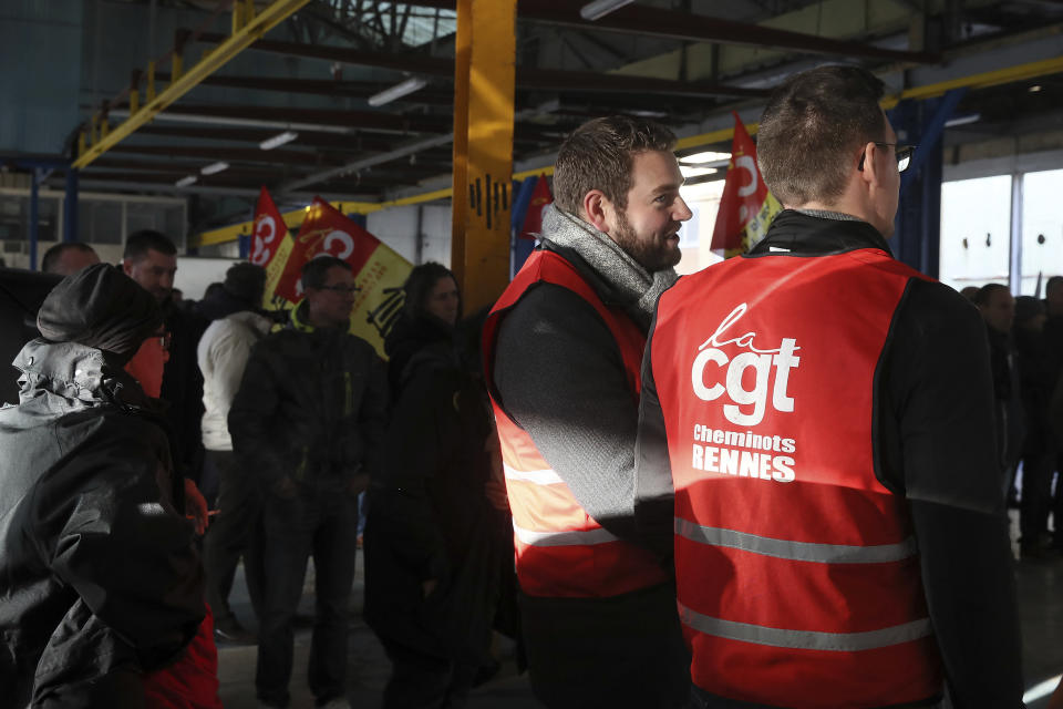 Railway workers gather during a meeting of the CGT union in Rennes, western France, Monday, Dec. 9, 2019. Unions launched nationwide strikes and protests over the government's plan to overhaul the retirement system. Paris commuters inched to work Monday through exceptional traffic jams, as strikes to preserve retirement rights halted trains and subways for a fifth straight day. (AP Photo/David Vincent)
