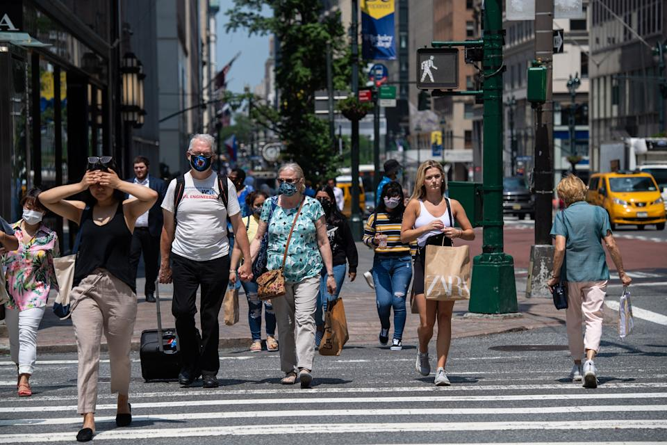 People walk down 5th Avenue on a warm day on June 7, 2021 in New York City. (Photo by Angela Weiss / AFP) (Photo by ANGELA WEISS/AFP via Getty Images)