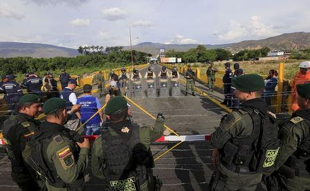 Colombian policemen stand guard in front of the border with Venezuelan policemen Bolivarianos near Villa del Rosario village