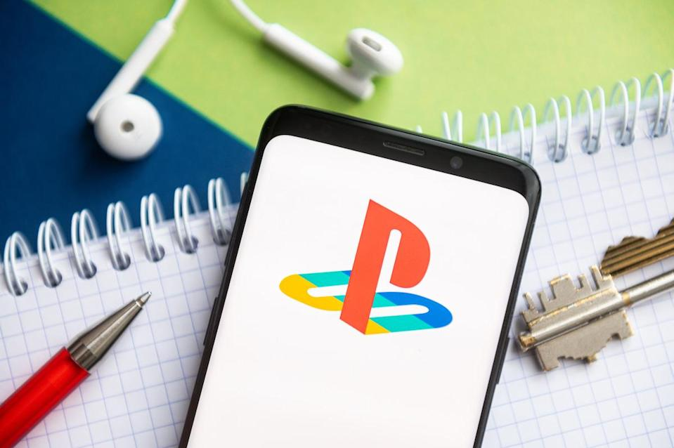 POLAND - 2021/02/09: In this photo illustration, a PlayStation logo seen displayed on a smartphone with a pen, key, book and headsets in the background. (Photo Illustration by Mateusz Slodkowski/SOPA Images/LightRocket via Getty Images)