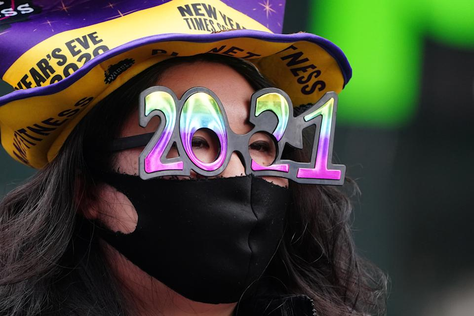 A woman wears '2021' numeral glasses in advance of New Year's eve in Times Square amid the coronavirus disease (COVID-19) pandemic in the Manhattan borough of New York City, New York, U.S., December 21, 2020. REUTERS/Carlo Allegri