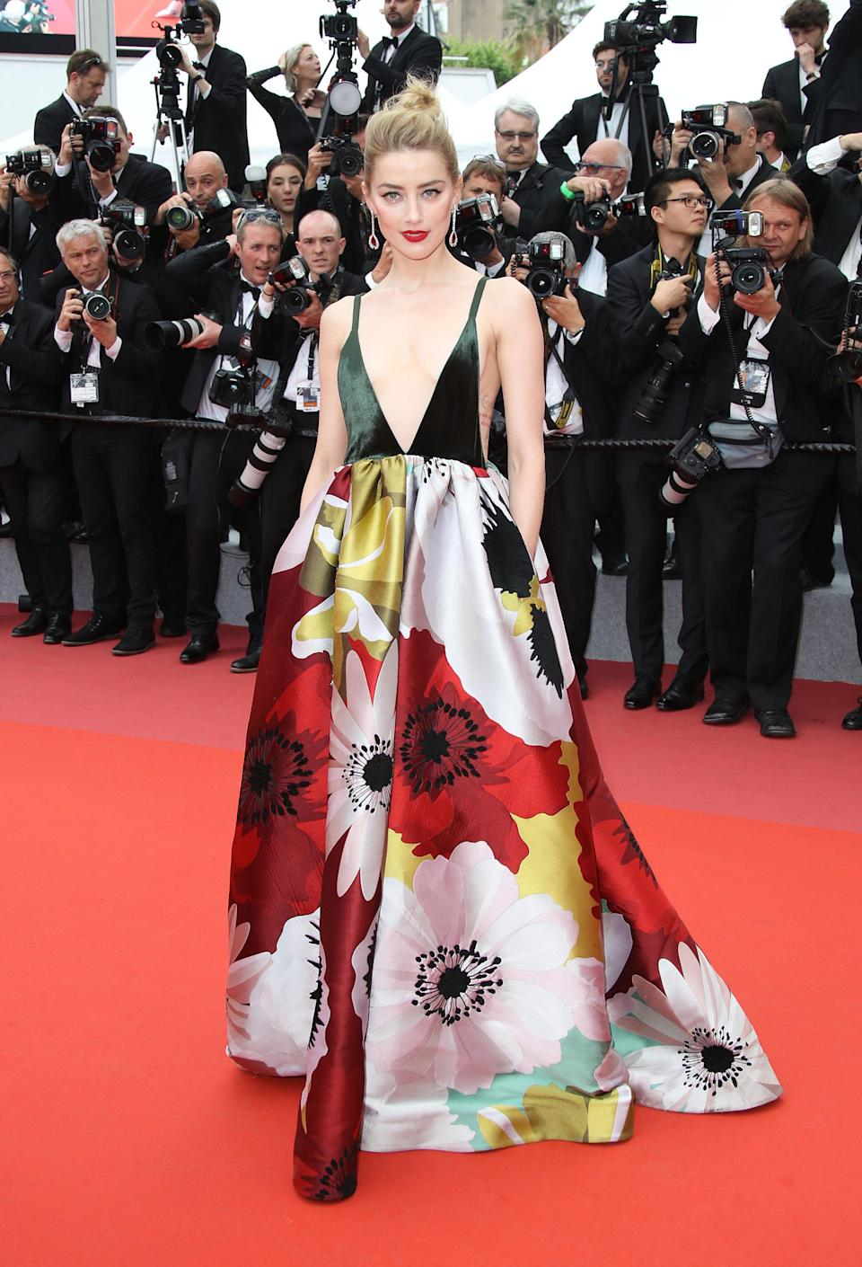 <p>Amber Heard look impeccable in a plunging floral print gown by Valentino. <em>[Photo: Getty]</em> </p>