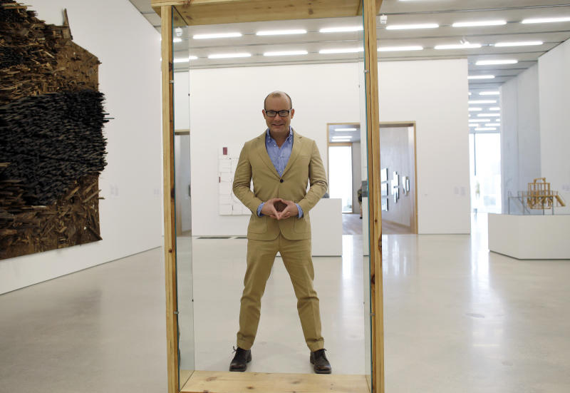 """In this Thursday, Dec. 12, 2013 photo, Thom Collins, director of the Perez Art Museum Miami, poses for a photograph at the museum standing by a piece by artist Robert Morris called """"Untitled (Pine Portal with Mirrors)"""" in Miami. The museum, called the PAMM by locals, opened in December and is becoming a must-see destination for tourists and locals alike with its eclectic and provocative collection. (AP Photo/Lynne Sladky)"""