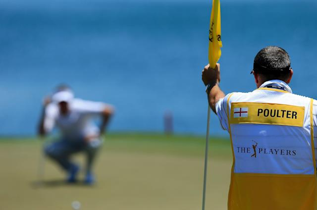 PONTE VEDRA BEACH, FL - MAY 10: Caddie Terry Mundy (R) holds the flag as Ian Poulter (L) of England lines up his putt on the 18th hole during the first round of THE PLAYERS Championship held at THE PLAYERS Stadium course at TPC Sawgrass on May 10, 2012 in Ponte Vedra Beach, Florida. (Photo by David Cannon/Getty Images)