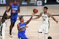 Orlando Magic's Markelle Fultz (20) shoots as Milwaukee Bucks' Giannis Antetokounmpo (34) and Marvin Williams defend during the first half of an NBA basketball first round playoff game Saturday, Aug. 29, 2020, in Lake Buena Vista, Fla. (AP Photo/Ashley Landis)
