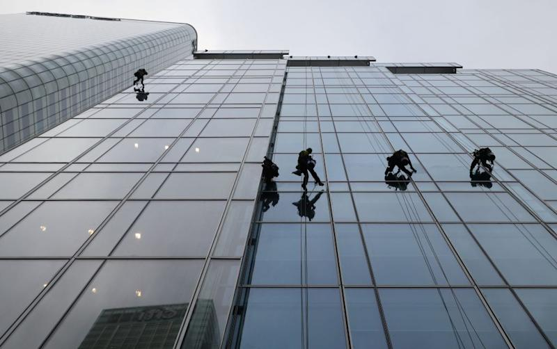 Workers clean the windows of scandal-ridden accounting giant KPMG's London skyscraper.