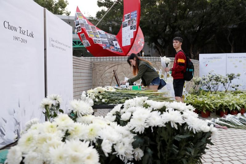 Students pay tribute with flowers to Chow Tsz-lok, 22, a university student who fell during protests at the weekend and died early on Friday morning, at the Hong Kong University of Science and Technology, in Hong Kong
