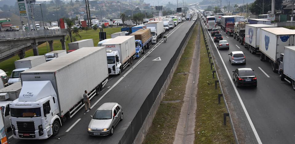 Truck drivers block the Regis Bittencourt road, 30 km from Sao Paulo, on May 26, 2018 during a strike to protest rising fuel costs in Brazil that has left much of the country paralyzed. - Brazil's government raised the stakes in its tense standoff with striking truckers Friday, ordering troops onto the streets to clear the huge blockades. The country's economic capital of Sao Paulo declared a state of emergency, the auto industry shut down, gas stations ran out of fuel and dozens of flights were canceled on the fifth day of the protest Friday. (Photo by Nelson ALMEIDA / AFP)        (Photo credit should read NELSON ALMEIDA/AFP via Getty Images)