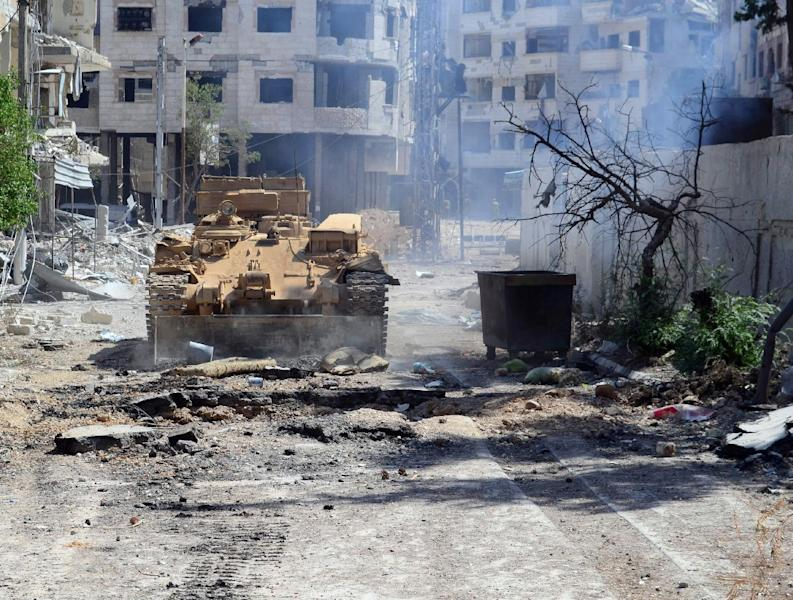 A picture released by the official Syrian Arab News Agency on August 14, 2014, shows an army tank advancing in a street in Mleiha, on the outskirts of the Damascus (AFP Photo/)