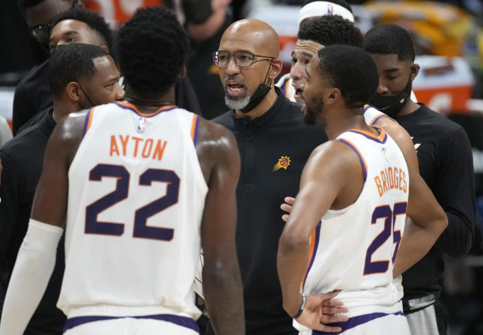 Phoenix Suns head coach Monty Williams, center, confers with players during a timeout late in the second half of Game 4 of an NBA second-round playoff series against the Denver Nuggets, Sunday, June 13, 2021, in Denver. Phoenix won 125-118 to sweep the series. (AP Photo/David Zalubowski)