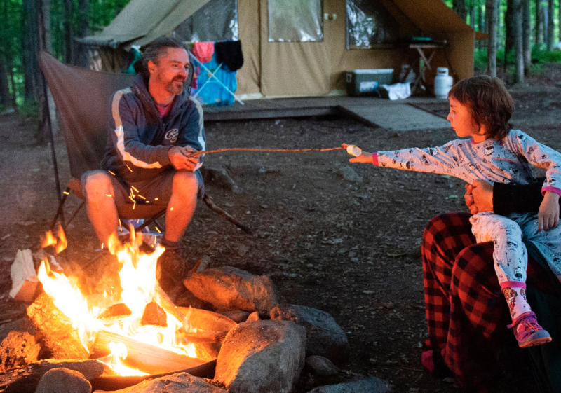 A family enjoys a campfire at the Huttopia Sutton glamping ground in Quebec, Canada, on August 14, 2019. (Photo: SEBASTIEN ST-JEAN/AFP via Getty Images)