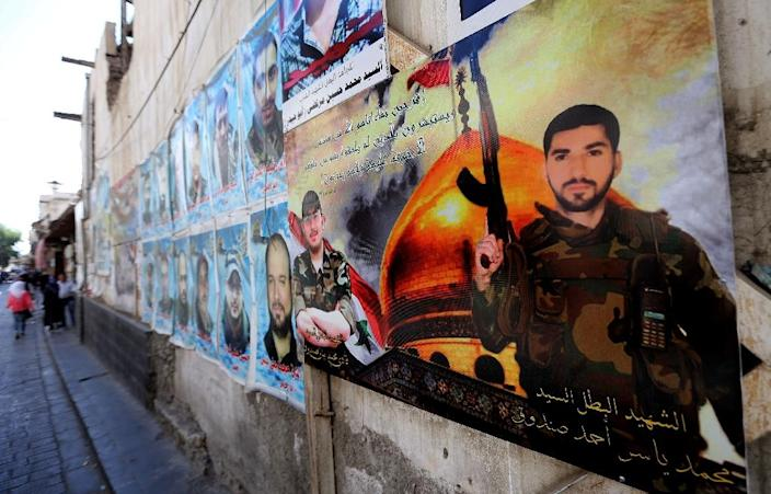 Portraits of pro-government forces members killed in combat are displayed on a street in the Syrian capital, Damascus, on September 21, 2015 (AFP Photo/Joseph Eid)