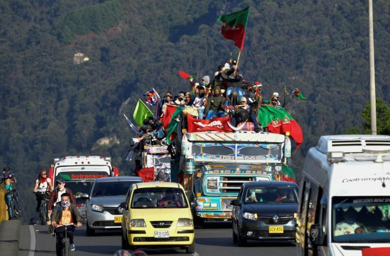 """Colombian indigenous people arrive in Bogota on """"chivas"""" (local transport vehicles) on October 18, 2020 to demand a meeting with Colombian President Ivan Duque"""