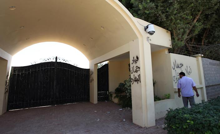 """A Libyan man walks past by the U.S. consulate's main gate, after an attack that killed four Americans, including Ambassador Chris Stevens on the night of Tuesday, Sept. 11, 2012, in Benghazi, Libya, Thursday, Sept. 13, 2012. The American ambassador to Libya and three other Americans were killed when a mob of protesters and gunmen overwhelmed the U.S. Consulate in Benghazi, setting fire to it in outrage over a film that ridicules Islam's Prophet Muhammad. Ambassador Chris Stevens, 52, died as he and a group of embassy employees went to the consulate to try to evacuate staff as a crowd of hundreds attacked the consulate Tuesday evening, many of them firing machine-guns and rocket-propelled grenades. Arabic writing reads """" Villa of Jamal al Beshary"""". which was written by the original owner to protect the property from another attack. (AP Photo/Mohammad Hannon)"""