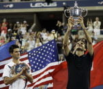 FILE - In this Sept. 9, 2007, file photo, Novak Djokovic, left, of Serbia applauds as Roger Federer of Switzerland holds up the championship trophy after winning the men's finals at the U.S. Open tennis tournament in New York. Federer is sure that Djokovic and Rafael Nadal will surpass his men's record for most Grand Slam titles, and he's ok with that. (AP Photo/Elise Amendola, File)