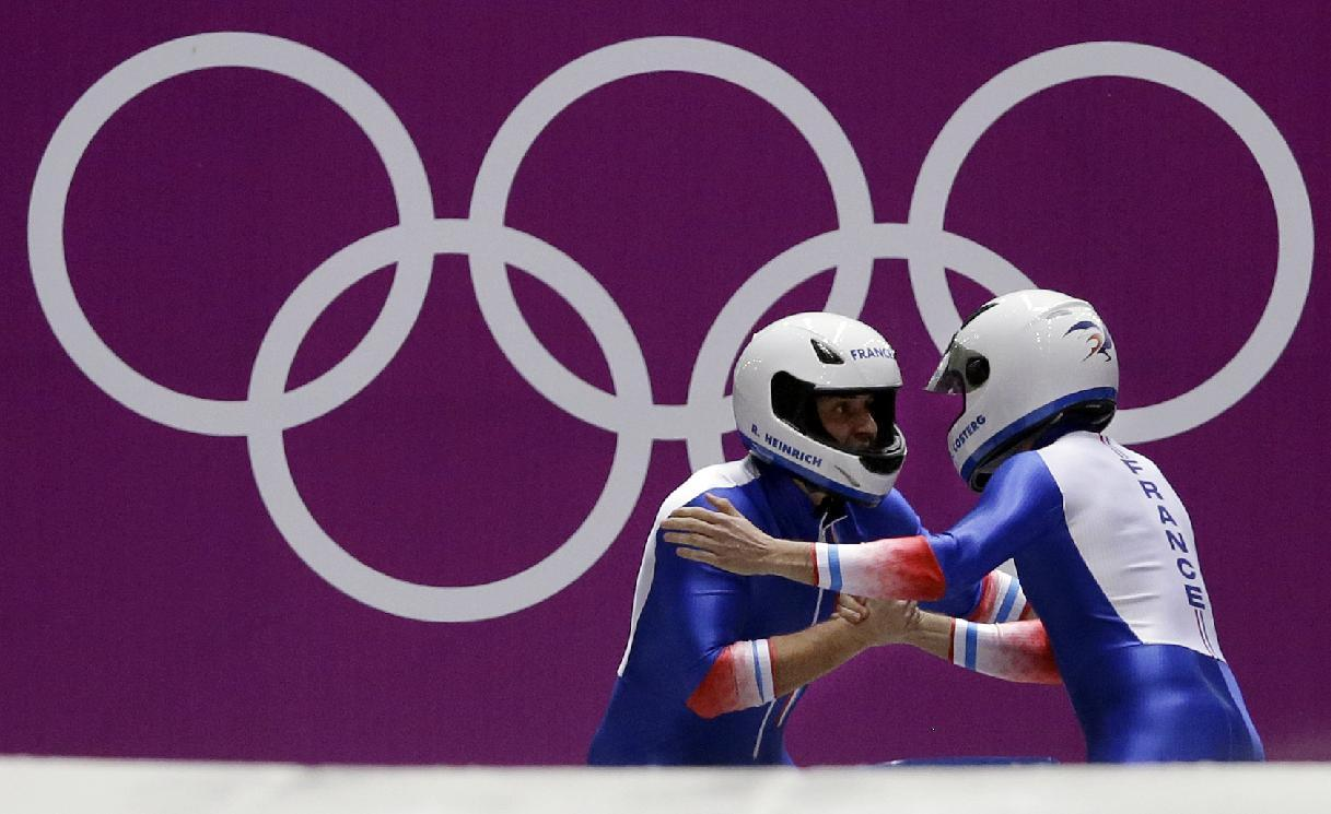 The team from France FRA-1, piloted by Loic Costerg and brakeman Romain Heinrich,  prepare to start their first run during the men's two-man bobsled competition at the 2014 Winter Olympics, Sunday, Feb. 16, 2014, in Krasnaya Polyana, Russia. (AP Photo/Dita Alangkara)