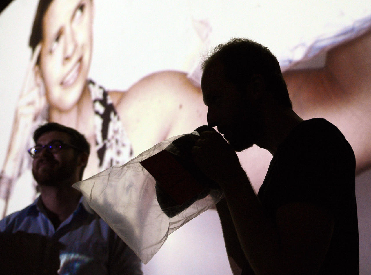 A partygoer smells a bagged shirt during a pheromone party, Friday, June 15, 2012, in Los Angeles. The get-togethers, which have been held in New York and Los Angeles and are planned for other cities, require guests to submit a slept-in T-shirt that will be sniffed by other participants. Then you can pick your partner based on scent. (AP Photo/Mark J. Terrill)
