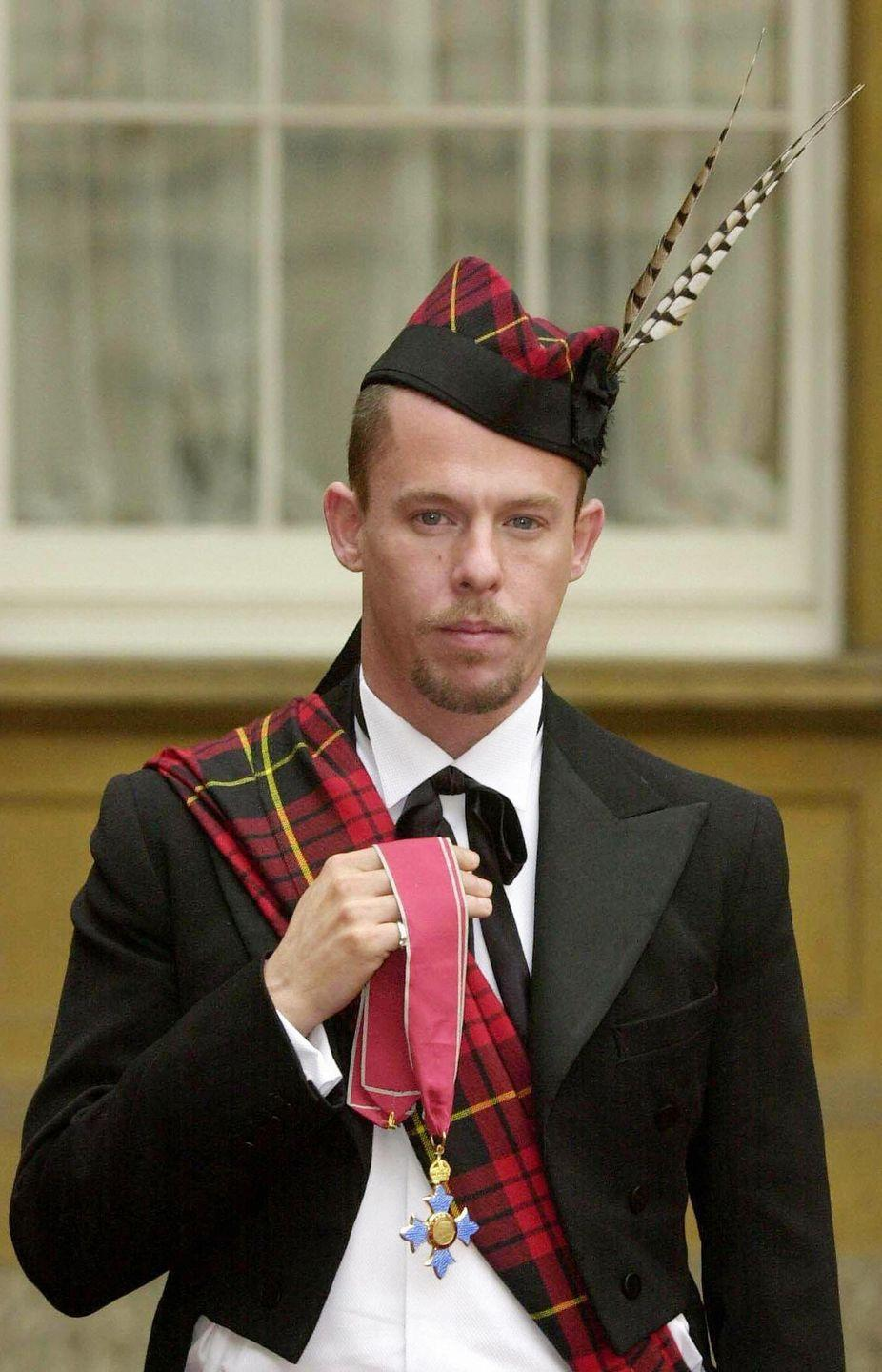 <p>British fashion designer Alexander McQueen chose to honor his heritage and sported a tartan sash and matching hat when he was awarded an OBE by Queen Elizabeth.</p>