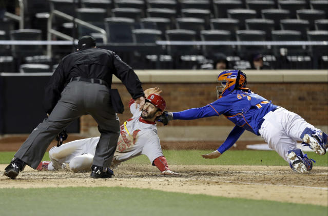 New York Mets catcher Travis d'Arnaud, right,tags out St. Louis Cardinals' Matt Carpenter (13) as home plate umpire Marty Foster watches the play during the ninth inning of a baseball game on Wednesday, April 23, 2014, in New York. The Mets won the game 3-2. (AP Photo/Frank Franklin II)