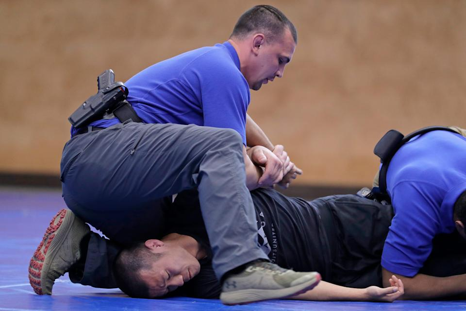 In this June 4, 2020, photo, Brandon Wilson, upper left, an instructor at the Washington State Criminal Justice Training Commission facility in Burien, Washington, restrains fellow instructor Ben Jia, lower left, during a demonstration for The Associated Press on takedown and restraint techniques taught to law enforcement officers.