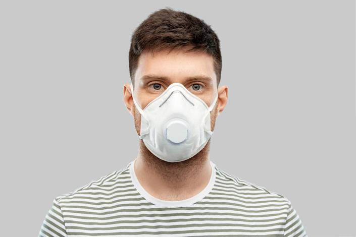 man in protective mask or respirator with valve over grey background