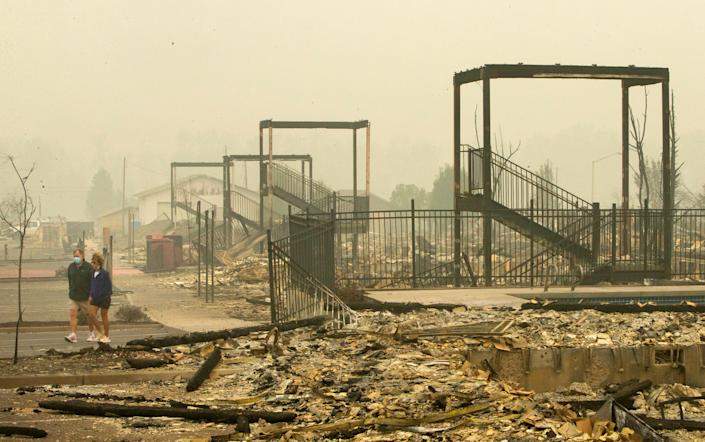 Rick Almand, left, and his ex-wife Carol Barton walk past the remains of stairways in an apartment complex in Talent, Ore. Sept. 12, 2020 where Almand lived before the Almeda Fire destroyed it. Almand defied police orders to leave the area the day of the fire to rescue his cat, Roo, moments before flames engulfed the complex. Both survived.