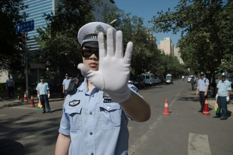 Chinese police officers block the road leading to the Philippines embassy in Beijing after an international court ruled against China in a Philippine challenge over Beijing-occupied territory in the South China Sea