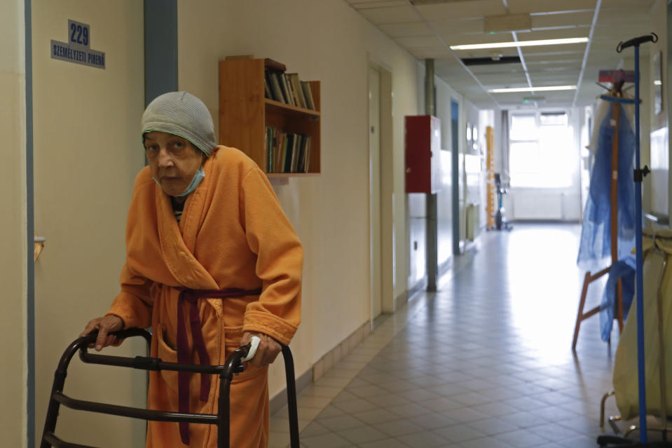 An elderly homeless woman walks in the corridor of the hospital for the homeless in Budapest, Hungary, Wednesday, April 14, 2021. A bitter conflict has emerged between Hungary's right-wing government and the liberal leadership of the country's capital city over a hospital for the homeless that may soon have to close. The Budapest hospital provides medical and social services and shelter to more than 1,000 people annually. But the Hungarian government has ordered it to vacate the state-owned building it occupies. Budapest's mayor says the eviction will risk the lives of the hospital's homeless patients as Hungary struggles with a deadly COVID-19 surge. (AP Photo/Laszlo Balogh)