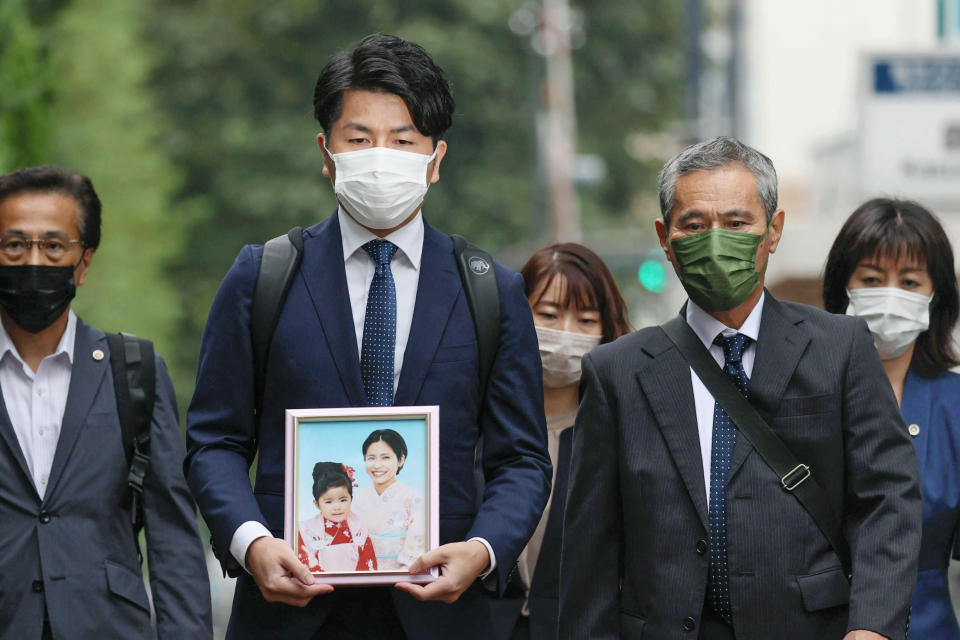 Takuya Matsunaga, second from left, holding a portrait of his wife Mana Matsunaga and daughter Riko Matsunaga, who were killed in a car accident in 2019, walks toward Tokyo District Court to hear the court's ruling on the driver Kozo Iizuka, in Tokyo Thursday, Sept. 2, 2021. The court on Thursday sentenced Iizuka, a 90-year-old former top bureaucrat, to five years in prison in the fatal car accident on a busy Tokyo street in a high-profile case in a fast-aging country where elderly driving has become a major safety concern. (Shinji Kita/Kyodo News via AP, File)(Kyodo News via AP)