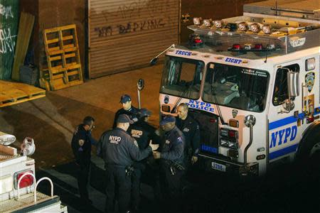 New York Police Department Officers depart a multiple shooting crime scene on Maujer Street in the Brooklyn borough of New York