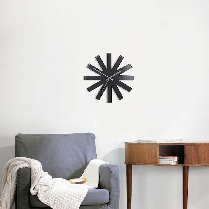 """A modern home calls for modern wall clocks, and this steel clock fits the bill. It's called the ribbon clock because the starburst design was inspired by the way ribbons look when wrapping a present. The clock measures 12.6 inches in diameter and is available in black (pictured) or steel. $45, West Elm. <a href=""""https://www.westelm.com/products/ribbon-wall-clock-d9532/?pkey=cclocks"""" rel=""""nofollow noopener"""" target=""""_blank"""" data-ylk=""""slk:Get it now!"""" class=""""link rapid-noclick-resp"""">Get it now!</a>"""