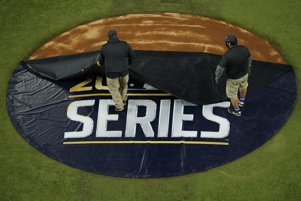 Members of the grounds crew uncover the pitcher's mound before Game 3 of the baseball World Series between the Los Angeles Dodgers and the Tampa Bay Rays Friday, Oct. 23, 2020, in Arlington, Texas. (AP Photo/David J. Phillip)