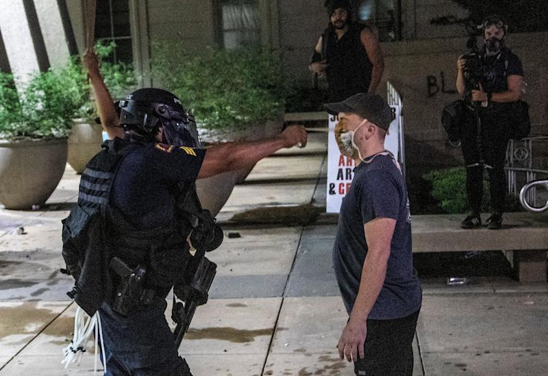 """A protester is pepper-sprayed at point blank range as police in riot gear <a href=""""https://www.huffingtonpost.ca/entry/protests-ramped-up-police-attacks_n_5ed316e9c5b640cb8341c6bb"""">deployed tear gas, pepper spray and smoke bombs</a> against demonstrators in downtown Raleigh on May 30, 2020."""