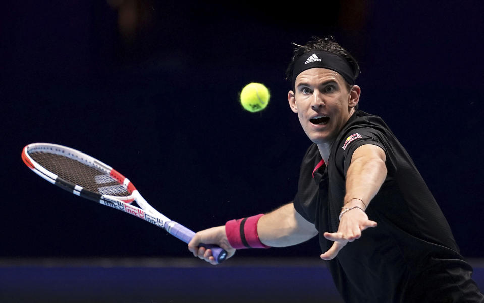 Austria's Dominic Thiem returns a shot to Greece's Stefanos Tsitsipas, during their London 2020 group singles match on day one of the ATP Finals tennis championship at the O2 Arena, London, Sunday Nov. 15, 2020. (John Walton/PA via AP)