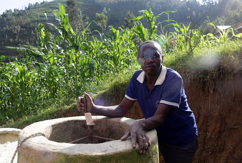 Etiene Twagirayezu, 60, talks about his biogas digester in front of his home in Rutabo, Rwanda, on November 18, 2017. Twagirayezu says that before his digester, he'd spend up to 3 hours a day gathering 10 kilograms of wood, and saw kids get injured climbing trees and be late to school doing the same. He added he was happy his workload at home was reduced due to being able to use his cow's and pig's poo instead of wood as fuel, as well as about the resulting decrease of deforestation. (Photograph by Yana Paskova)