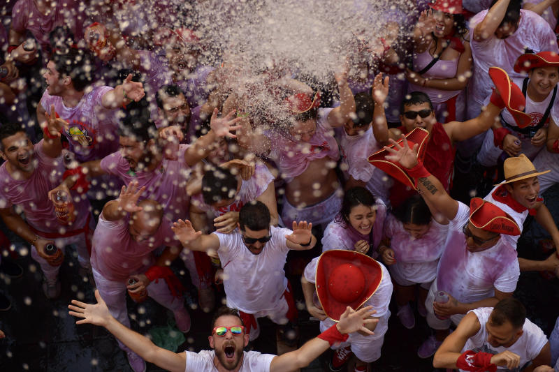 Revellers celebrate while waiting for the launch of the 'Chupinazo' rocket, to celebrate the official opening of the 2019 San Fermin fiestas with daily bull runs, bullfights, music and dancing in Pamplona, Spain, July 6, 2019. (Photo: Alvaro Barrientos/AP)