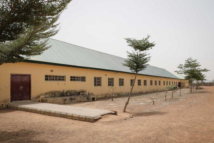 A long single storey building is seen with small trees planted in a row running along its side.