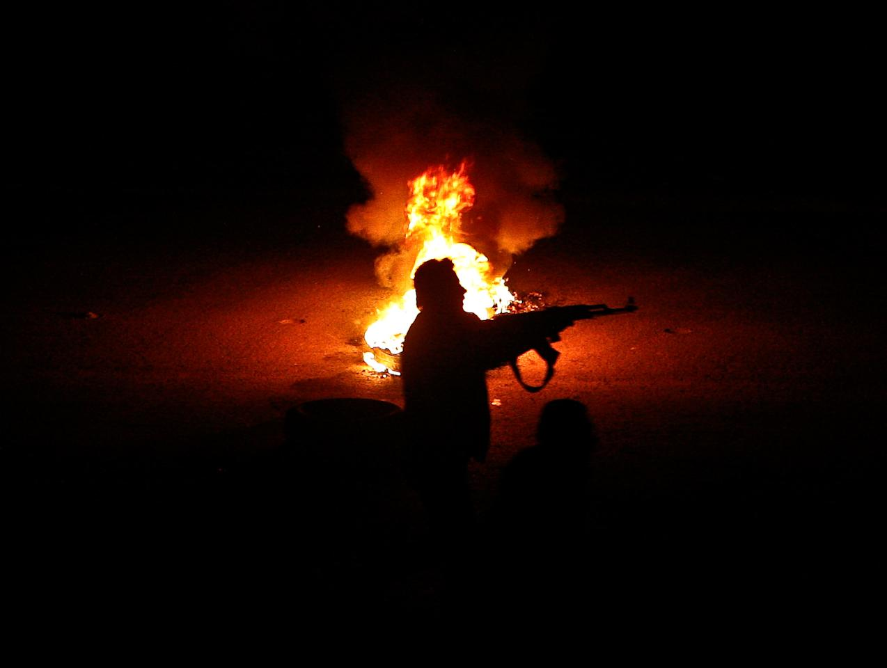 A Syrian rebel stands next to a flaming tire while firing at a Syrian army checkpoint, in a suburb of Damascus, Syria, on Saturday, March 17, 2012. Two suicide bombers detonated cars packed with explosives in near-simultaneous attacks on heavily guarded intelligence and security buildings in the Syrian capital Damascus Saturday, killing at least 27 people. (AP Photo)