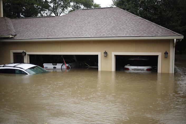 A house and vehicles stand in floodwaters in Spring, Texas.