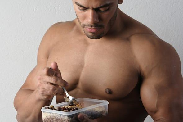 Male fitness Model eating healthy bodybuilding diet food out of tupperware and jug of water