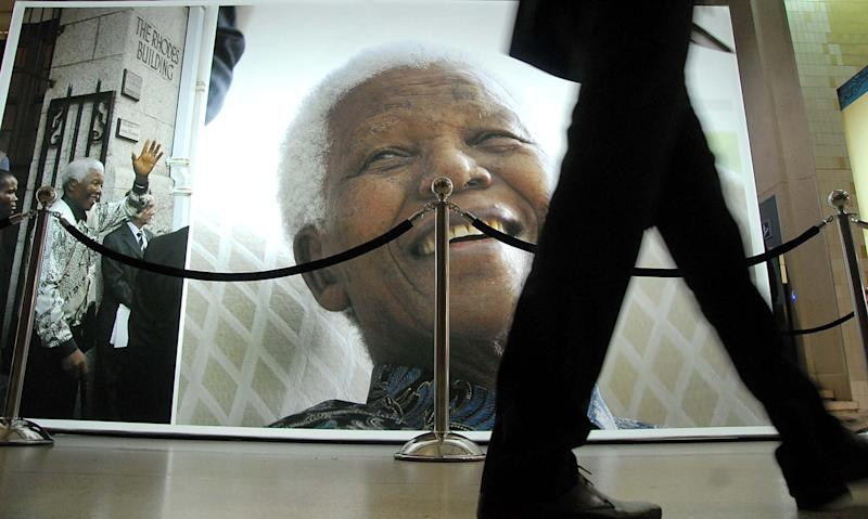 People pass photos of former South Africa President Nelson Mandela at the Nelson Mandela Legacy Exhibition in Cape Town, South Africa, Tuesday, July 2, 2013. Mandela remains in critical condition in a Pretoria clinic . (AP Photo/Masixole Feni)