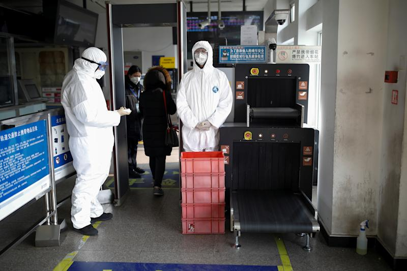 Staff members wearing protective suits and masks stand near the security check at a subway station, as the country is hit by an outbreak of the new coronavirus, in Beijing, China January 28, 2020. REUTERS/Carlos Garcia Rawlins