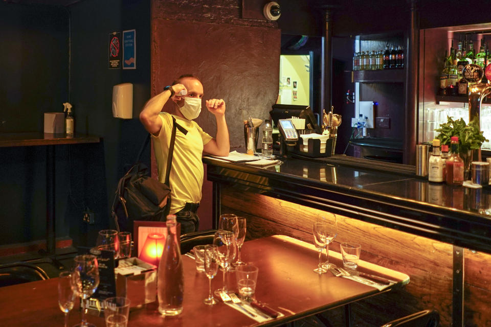 """A member of staff takes his temperature at The Piano Works club in Farringdon, London, Friday, July 16, 2021, in preparation for its reopening as part of the relaxation of COVID-19 restrictions. Thousands of young people plan to dance the night away at """"Freedom Day"""" parties as the clock strikes midnight Monday, when almost all coronavirus restrictions in England are due to be scrapped. Nightclubs can open fully and are not required to use vaccine passports. (AP Photo/Alberto Pezzali)"""