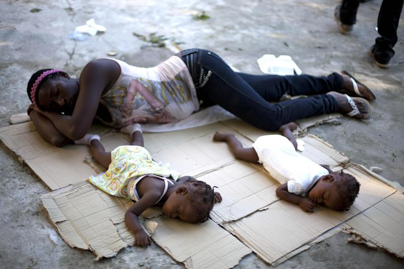 Marie Matte Mayan 26, sleeps on the floor with her twins, Maudeline and Maudena Pierre an a shelter after being deported by Dominican Republic authorities, in Croix-des-Bouquets, Haiti, Sunday Nov. 24, 2013. Dominican authorities expelled 244 Haitians after an elderly Dominican couple was slain in an apparent burglary near the border between the two countries and an angry mob retaliated by killing a Haitian man, Rev. Antoine Lissaint of Haiti's Jesuit Refugee and Migrant Organization said Sunday.(AP Photo/Dieu Nalio Chery)