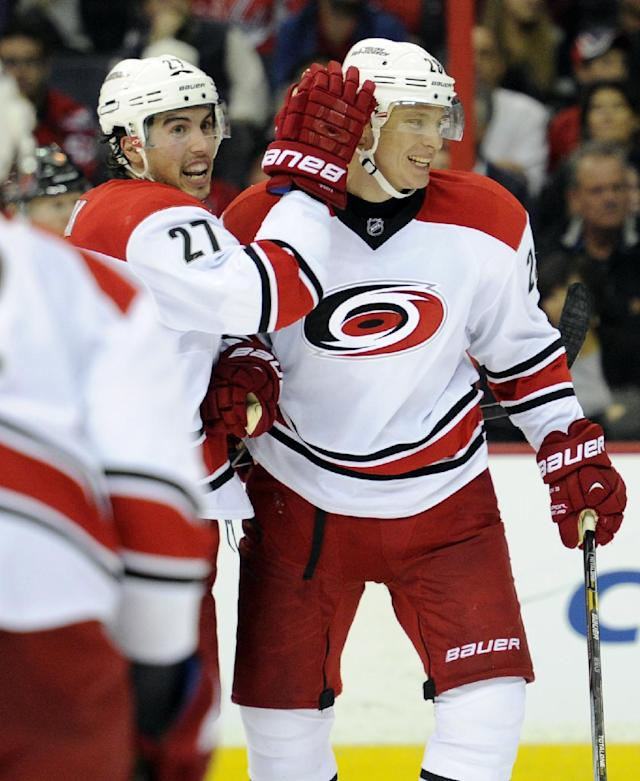 Carolina Hurricanes left wing Alexander Semin, right, of Russia, celebrates his goal with Justin Faulk (27) against the Washington Capitals during the second period an NHL hockey game, Thursday, Oct. 10, 2013, in Washington. (AP Photo/Nick Wass)