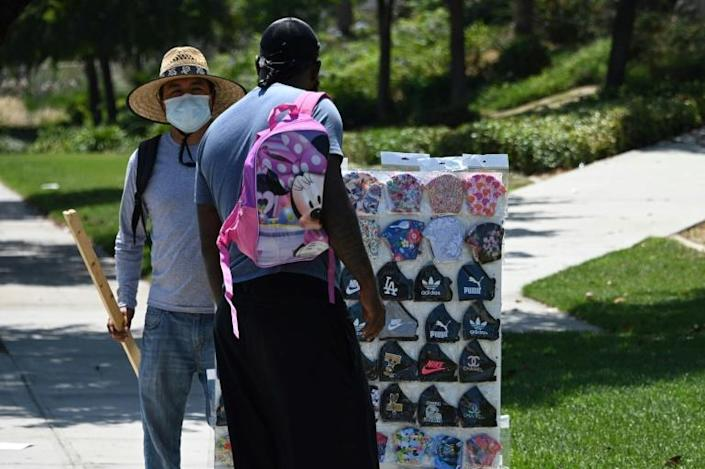 A man stops to look at masks for sale by a street vendor outside Walmart in Burbank, California (AFP Photo/Robyn Beck)